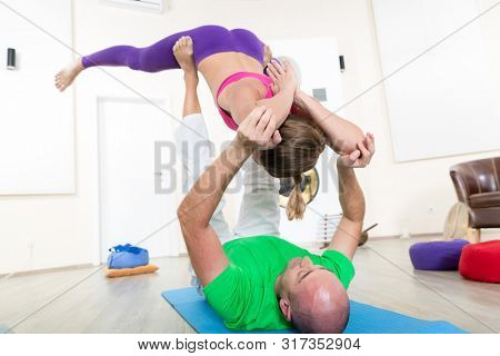 Man and woman doing acroyoga in class stock photo