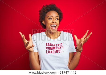 African american woman wearing sarcastic comments t-shirt over red isolated background celebrating crazy and amazed for success with arms raised and open eyes screaming excited. Winner concept stock photo
