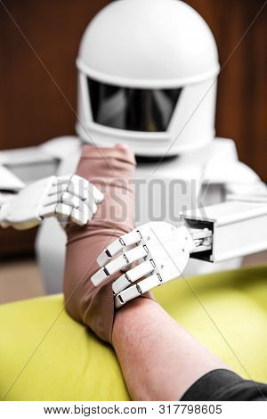 caregiver robot or medical assisted living robot is putting on a compression stocking on an senior adults leg stock photo