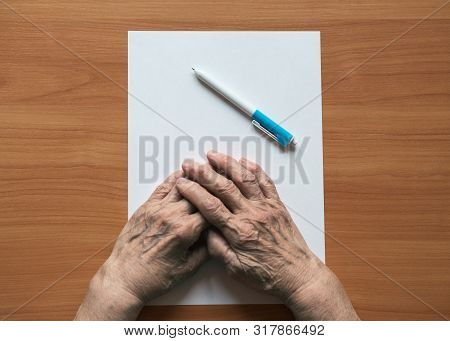 Pensioner writes in pen on paper. Senior citizen in front of a sheet of paper. Old woman pensioner writes on a piece of paper. stock photo