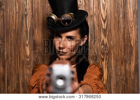 selective focus of serious steampunk woman in top hat with goggles aiming with pistol at camera on wooden stock photo