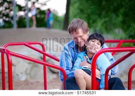Father playing with disabled son on merry go round at playground. Child has cerebral palsy. stock photo