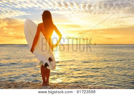 Surfing surfer girl looking at ocean beach sunset. Silhouette of female bikini woman looking at wate