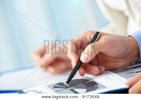 Close-up of business person hand with pen over document stock photo