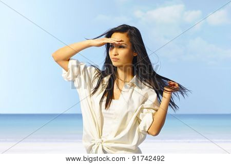 Portrait of attractive young Asian girl on the beach, shading eyes by hand. stock photo