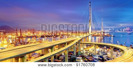 Container Cargo freight ship with working crane bridge in shipyard under Stonecutters highway bridge at sunset for Logistic Import Export, Hong kong stock photo