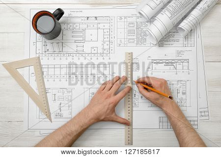 Close-up hands of architect while working process with centimeter ruler. Workplace of architect. Engineering work. Construction and architecture. Architect drawing.