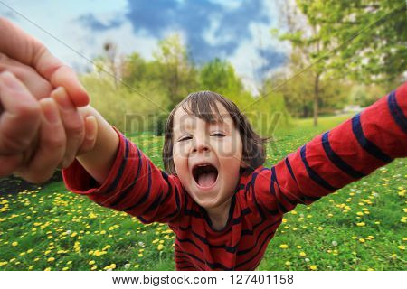 Adorable little boy, spinning in circle in the park, having fun with his mom, laughing, wide angle view stock photo