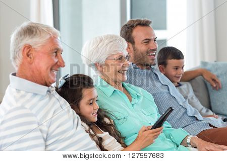 Happy family sitting on sofa watching television in their living room stock photo