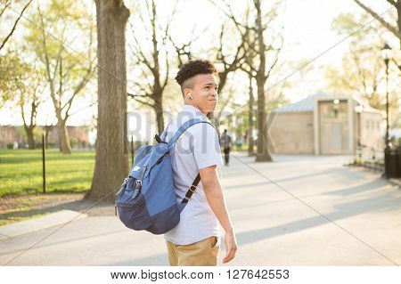 Young educated boy with packpack walk on college campus photographed in New York City in April 2016. stock photo