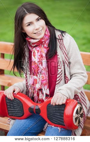 Female model holding modern red electric mini segway or hover board scooter in hands while sitting on a bench in green park. Popular new city transport. Girl is wearing trending boho style clothes. stock photo