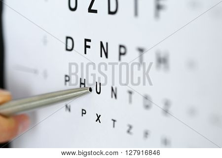 Silver ballpoint pen pointing to letter in eyesight check table. Sight test and correction excellent vision or optician shop laser surgery alternative driver health certificate examination concept stock photo