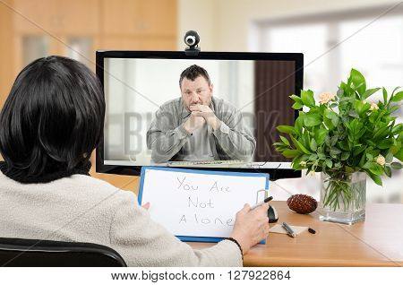 Middle aged man sitting in the monitor talks with psychotherapist via online video chat. He looking depressed. Black-haired psychiatrist holds written message for him - You are not alone. Horizontal indoors picture stock photo