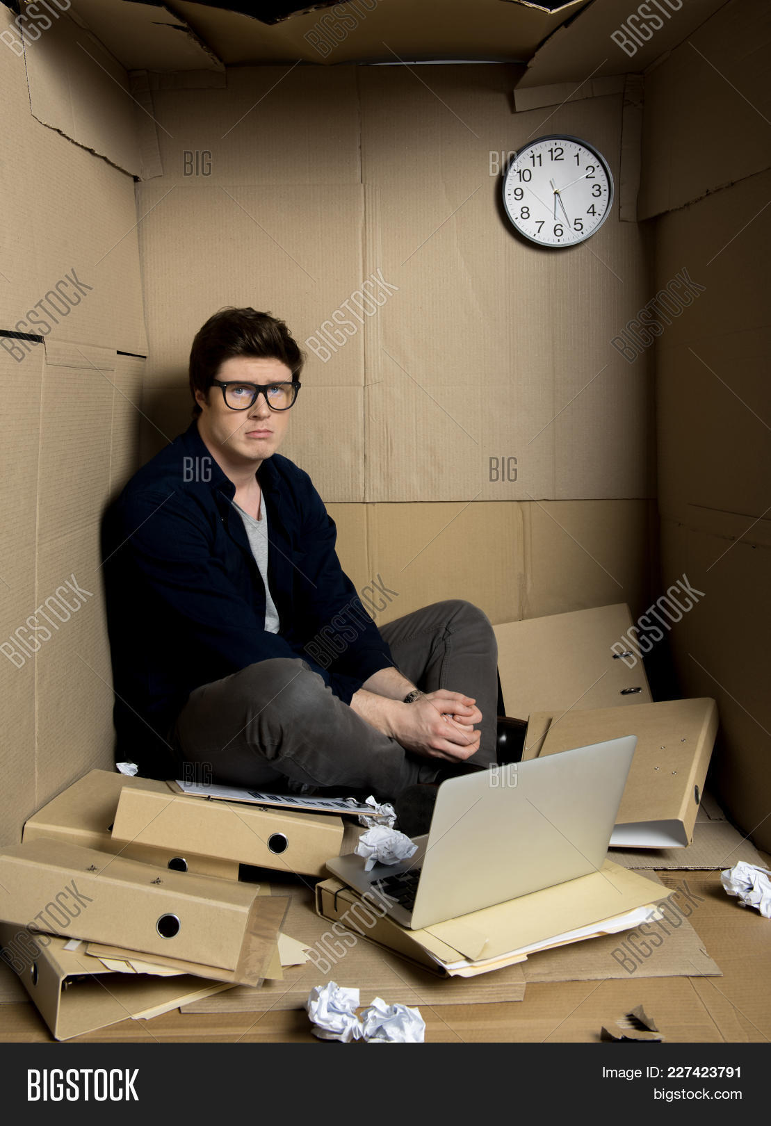 box,business,businessman,cardboard,carton,caucasian,chaos,concept,confined,cramped,crumpled,depressed,disappointed,discomfort,employee,frustrated,full,gadget,glasses,guy,hopeless,indoor,inside,laptop,length,little,male,man,manager,narrow,office,one,overcrowding,paper,pasteboard,portrait,restricted,room,sad,sit,small,space,straitened,technology,tight,tired,uncomfortable,unhappy,work,young