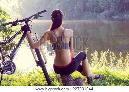 Girl cyclist with a mountain bike near the river sits and looks afar stock photo