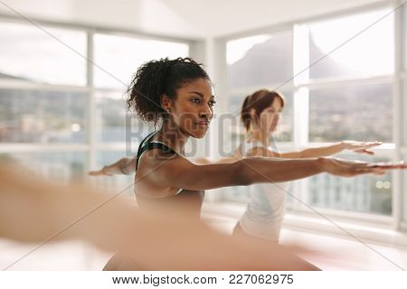 Women doing stretching and yoga workout at gym. Female trainer with her student during physical training session. stock photo