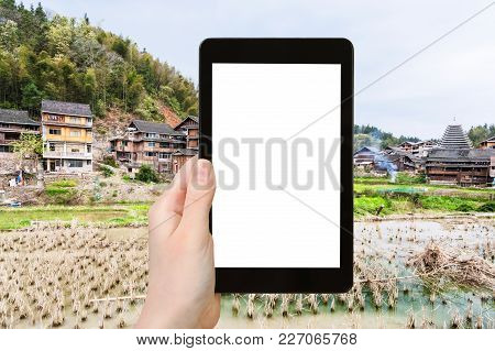 travel concept - tourist photographs rice paddy in Chengyang village of Sanjiang Dong Autonomous County in China in spring on tablet with cut out screen for advertising logo stock photo
