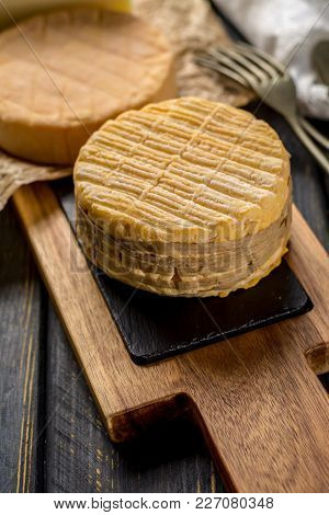 Tasting of oldest french AOC soft pudgent wrapped yellow cheese Livarot from Normandy, made from cow milk french cheese close up stock photo