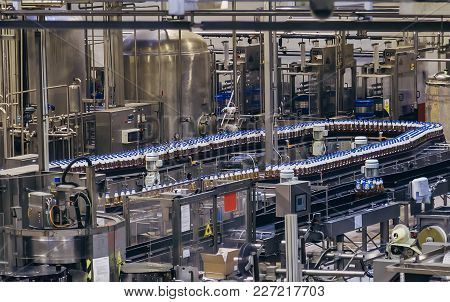 Conveyor belt of brewery production line . Beer polyethylene PET bottles are moving on conveyor. stock photo