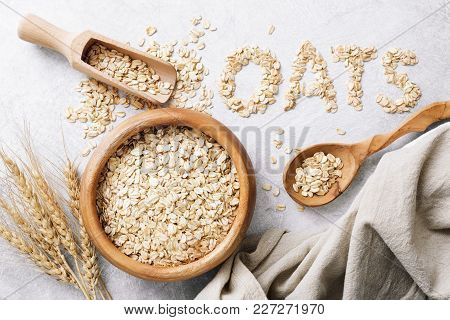 Rolled oats or oat flakes in wooden bowl on white background. Top view. Healthy lifestyle, healthy eating, dieting, weight loss concept stock photo