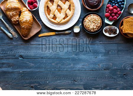 Top view of a wood table full of cakes, fruits, coffee, biscuits, spices and more breakfast classic sweet foods. stock photo