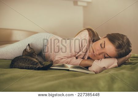 Beautiful woman fall asleep with her cat while reading a book. stock photo