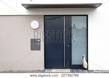 The angular and modern house entrance of a residential building with a steel door and a shelter. stock photo