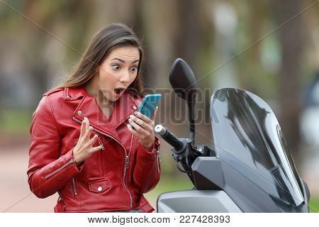 Amazed motorbiker reading exciting news on line in a smart phone on her motorbike stock photo