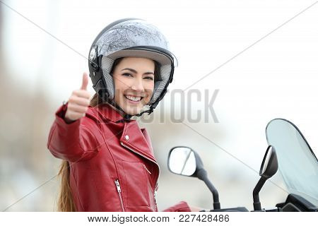 Satisfied motorbiker gesturing thumbs up on her motorcycle outdoors stock photo