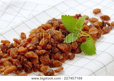 pile of sweet raisins on checkered dishtowel - close up stock photo