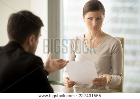 Millennial Businesswoman With Skeptical Facial Expression Holding Contract Document And Listening Un