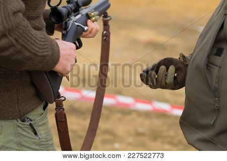 soldier give ammo to sniper, close up picture of rifle reloading stock photo