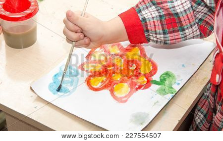 A Girl Draws A Drawing With Paints On A Sheet .