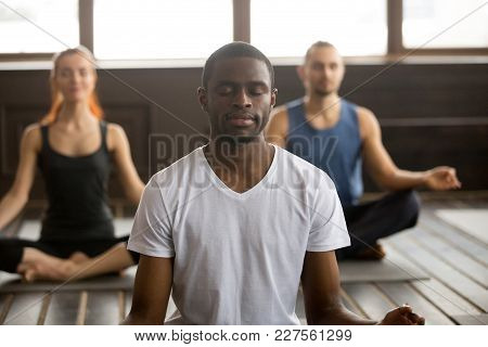 Young black man and a group of sporty people practicing yoga lesson with instructor, sitting in Sukhasana exercise, Easy Seat pose with mudra gesture, students training in club, working out, close up stock photo