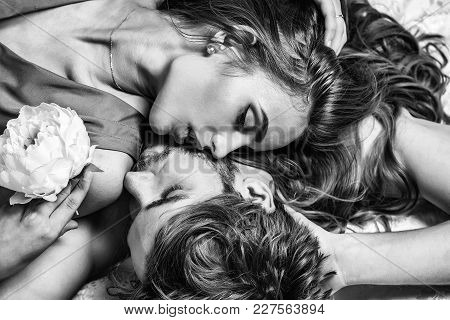 Sexy couple young beautiful cute lovers in love pretty girl and sexi man lying on back on white bedsheet on floor stock photo