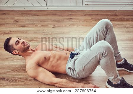 A handsome athletic male in sportswear doing exercise, lying on a wooden floor in the home. stock photo