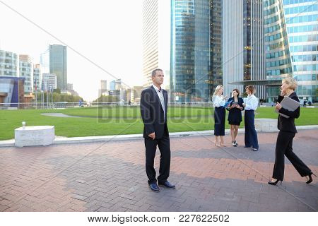 Male businessperson dressed in black suit looking at watch in La Defense Paris. Concept of work planning and time management. Employees of large organization advising and talking in background. stock photo