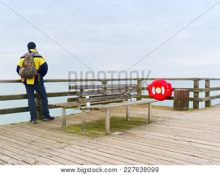 Man traveler with green backpack sit on wooden sea pier. Man in trekking suit in harbor in misty day. Touristic mole, wet wooden floor above sea. stock photo