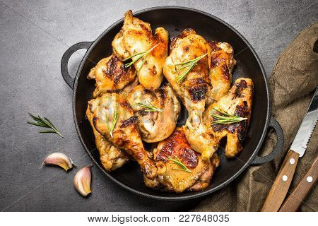 Baked Chicken Barbeque In Iron Pan On Dark Stone Table. Top View.