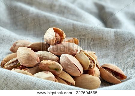 Top view close-up picture of pistachios on light grey fabric cotton napkin, shallow depth of field, selective focus, front focus. Useful nutritious and tasty food. Healthy lifestile concept. stock photo