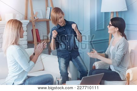 You are in a total norm now. Male youngster cannot keep his emotions inside while hearing his mother and a young psychologist clapping to him after showing tremendous psychological recovery results. stock photo