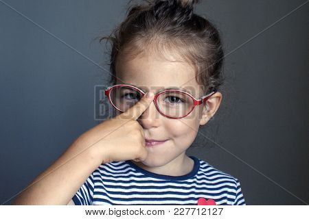 The child adjusts his glasses with his finger. Honors pupil. Correction of vision in preschool children. stock photo