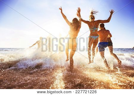 Big Crowd Of Friends Having Fun At Sunset Sea Beach. Beach Vacations Concept