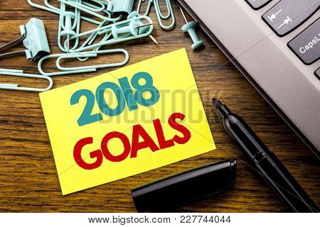 Handwriting text   2018 Goals. Concept for New Yer resolutions Written on sticky paper reminder, wooden background with sticky, one folded paper alone for difference or collaboration stock photo
