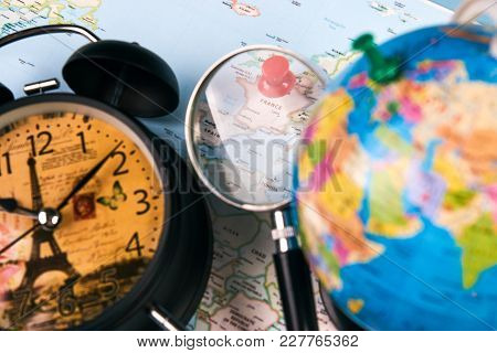 Planing for travel to France Paris with worldmap globe magnifying glass and alarm clock. Travel time in Europe concept. European holidays. traveling background with copy space. stock photo