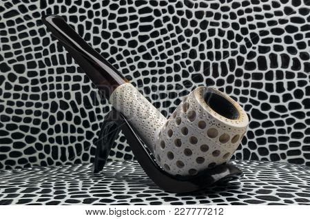 Biliard smoking tobacco pipe made from sea foam Meershaum mineral sepiolite against the background of imitation crocodile skin of black and white tones. On the stand stock photo