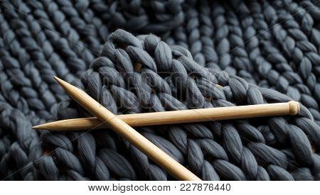 wooden knitting needles on background of grey merino wool blanket stock photo