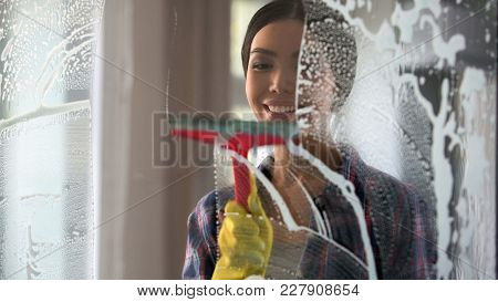 Good wife with pleasure cleaning house and washing room windows, order at home, stock footage stock photo