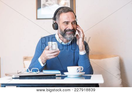 Senior old man listening to his favorite music through big headphones, enjoying the rich sound of the music, he's sitting in a coffee shop stock photo