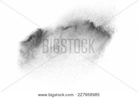 Black powder explosion against white background.The particles of charcoal splatted on white background. Closeup of black dust particles explode isolated on white background. stock photo
